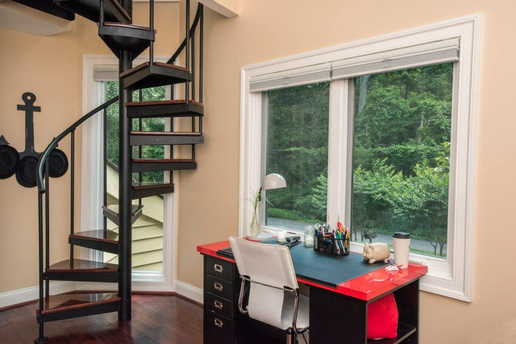 open frame steel spiral stair with dark wood